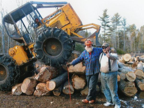 Two lumberjacks posing next to a pile of logs in Elizabethtown