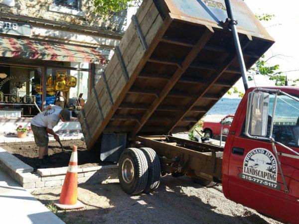A Thousand Islands Landscaping truck dumping dirt in Alexandria Bay