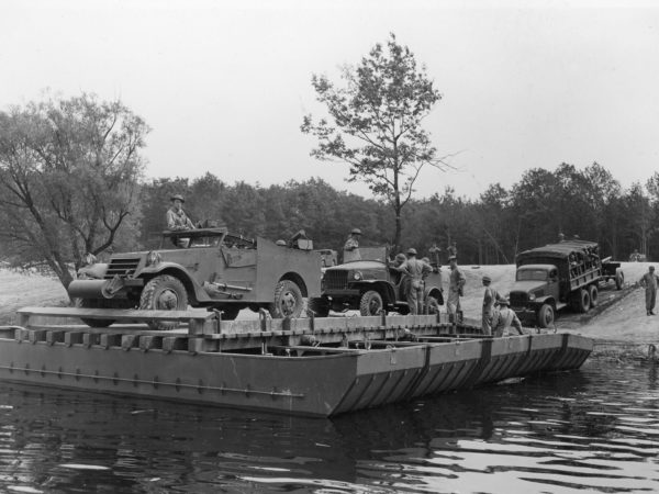 Soldiers loading vehicles and equipment onto a barge at Pine Camp
