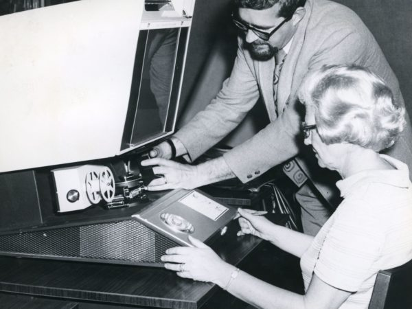 Reference assistants using a microfilm reader at Crandall Public Library in Glens Falls