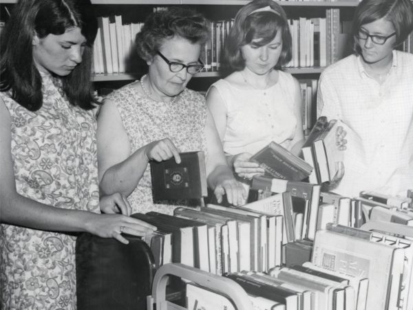 Library staff look over book cart at Crandall Public Library in Glens Falls