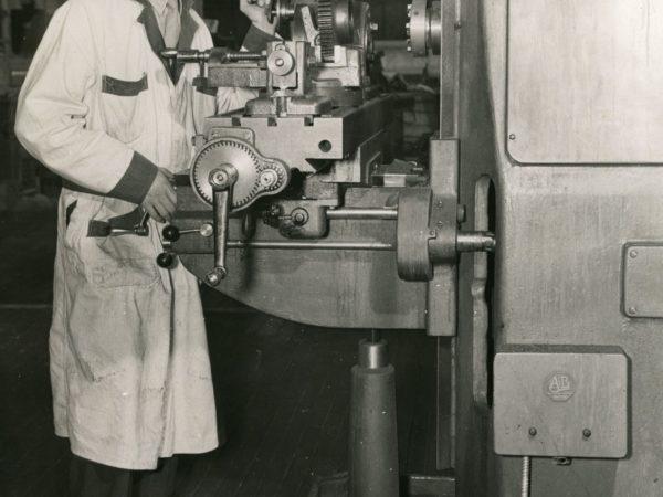 Man operating a lathe at the National Defense Aviation School in Glens Falls