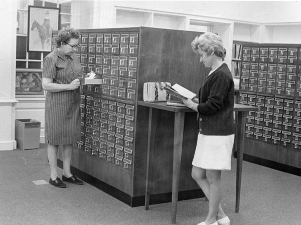 Reference Librarian and patron look through the card catalog at Crandall Public Library in Glens Falls