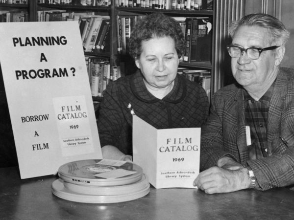 Librarian McAndrews shows film catalog to a patron at the Crandall Public Library in Glens Falls