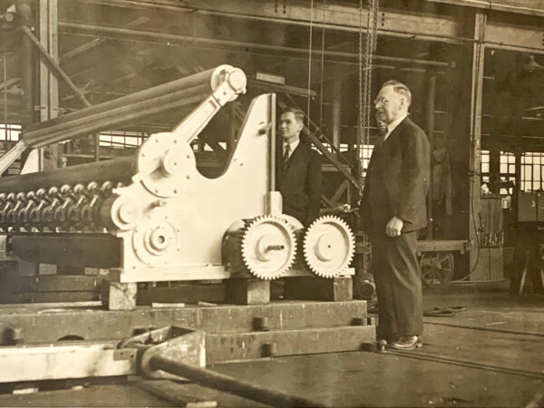 Draftsman Frans Alfred Helin (right) inspects machine at the Bagley & Sewall Company