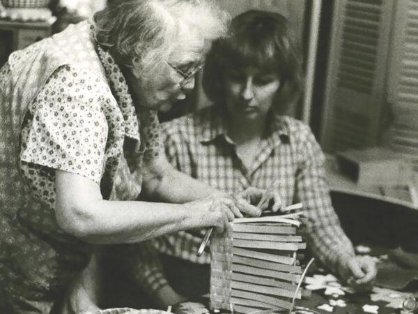 Woman demonstrates basket making technique