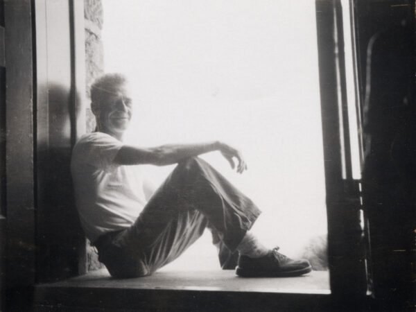 Gerald Heath sits in doorway or windowsill